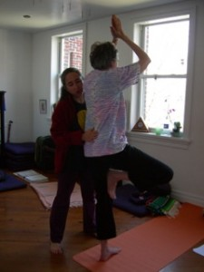 Bobbi helping student with a Tree Pose